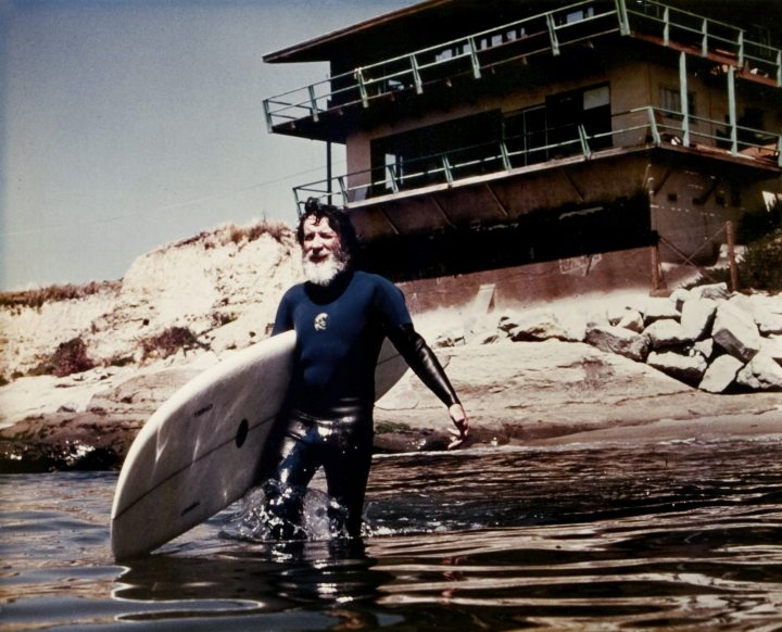 Jack O'Neill wading into the water with his surfboard