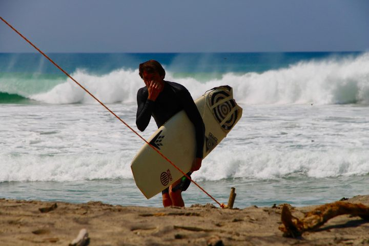 Chris Chaffing getting out of the surf holding a Firewire Vanguard surfboard